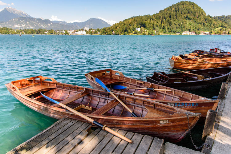 Boats moored by pier on lake