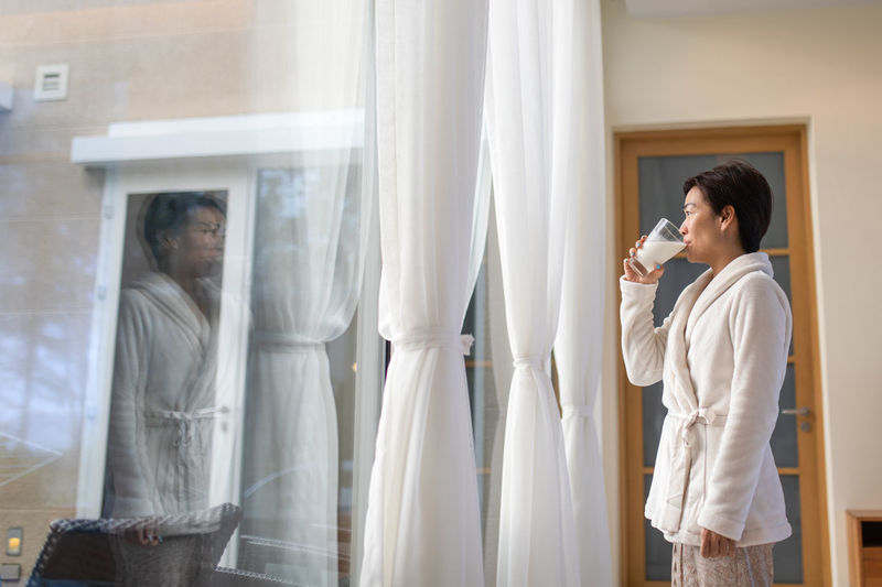 reflection on window Asian Woman Morning Woman Adult Contemplation Drinking Glass Drinking Milk Healthy Eating Holding Indoors  Lifestyles Looking Mid Adult One Person Profile View Reflection Robe Side View Standing Technology Three Quarter Length Waist Up Window Young Adult