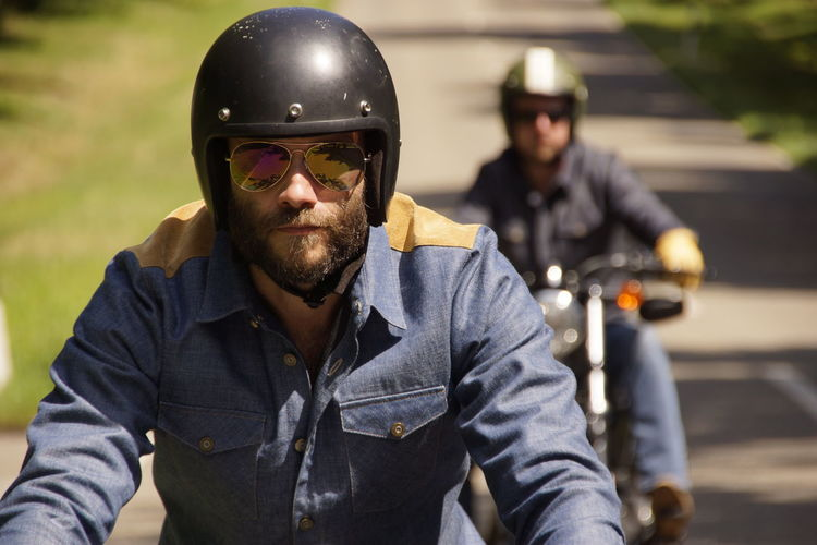 Man With Friend Riding Motorcycles On Road