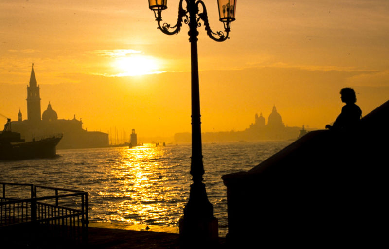 Italy, Venice, Piazza San Marco, San Giorgio Maggiore, Sunset with lantern Lantern Sunset San Giorgio Maggiore Piazza San Marco Venice Italy Orange Color Built Structure Sea Laguna Di Venezia  Sky Building Exterior Travel Destinations Outdoors Travel Cityscape Sun Silhouette Water City Nature Water Reflections Stairway Balustrade Lamppost EyeEmNewHere