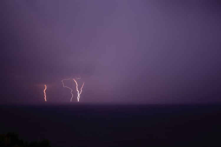 Scenic view of sea with lightning in sky at night