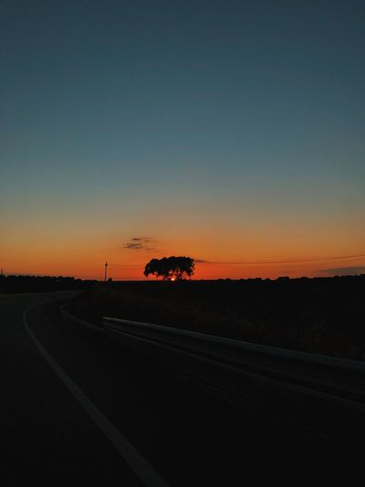 Silhouette road against sky during sunset
