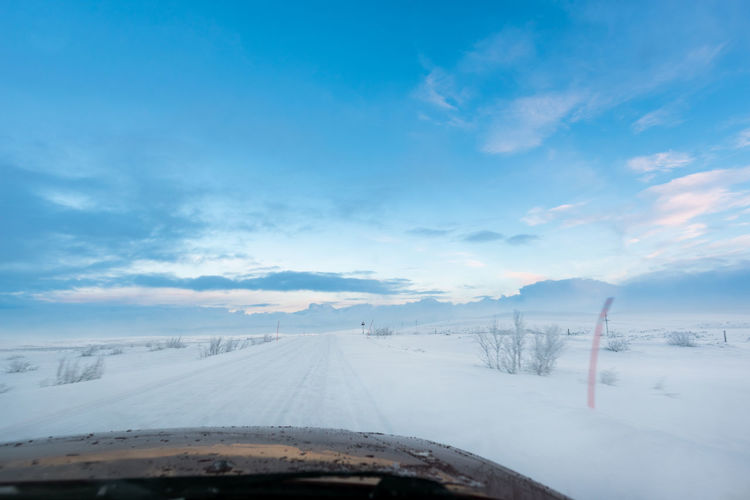 Driving on an ice road above the Arctic Circle Winter Sky Cold Temperature Snow Cloud - Sky Transportation Mode Of Transportation No People Nature Scenics - Nature Beauty In Nature Land Vehicle Environment Day Windshield Landscape White Color Car Point Of View Space For Text Space For Copy Driving Road Trip Remote Places Arctic Circle Ice Road