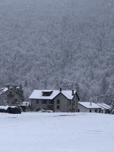 Snow covered landscape and houses against mountain