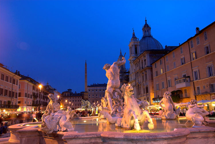 Fountain of neptune by old buildings against sky at dusk