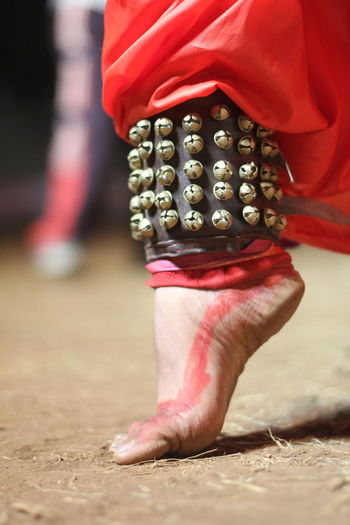 Low section of person wearing ghungroo dancing on dirt