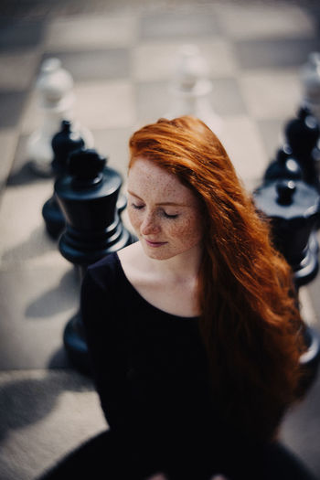 High Angle View Of Beautiful Redhead Woman Sitting With Eyes Closed Against Chess Board