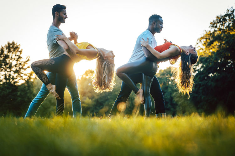 Dancing couples in a park during sunset Group Of People Friendship Sunset People Outdoors Dance Dancing Dance Teacher Kizomba Dance School Couples Park Grass Meadow Backlit Fun Positive Emotion Dancer Goldenhour