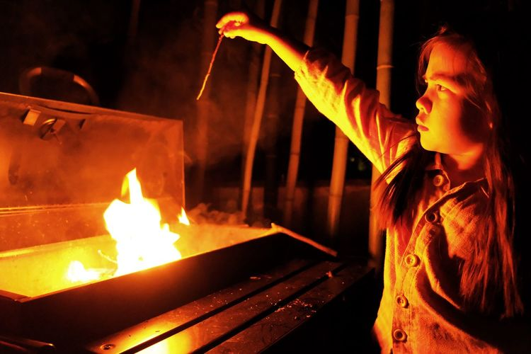 Girl standing by fire