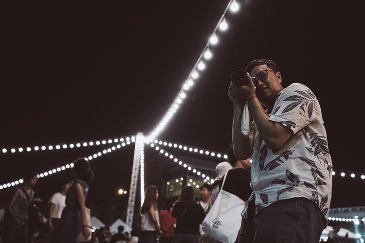 Low angle view of man photographing while standing against sky at night