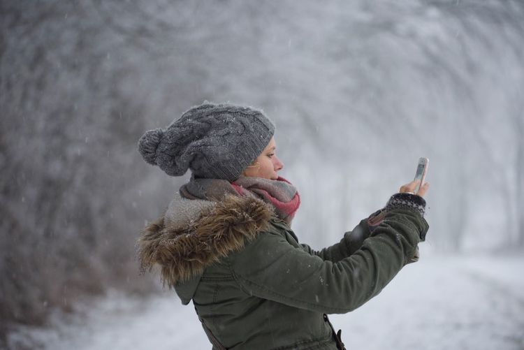 Side View Of Woman Photographing Through Smart Phone During Winter