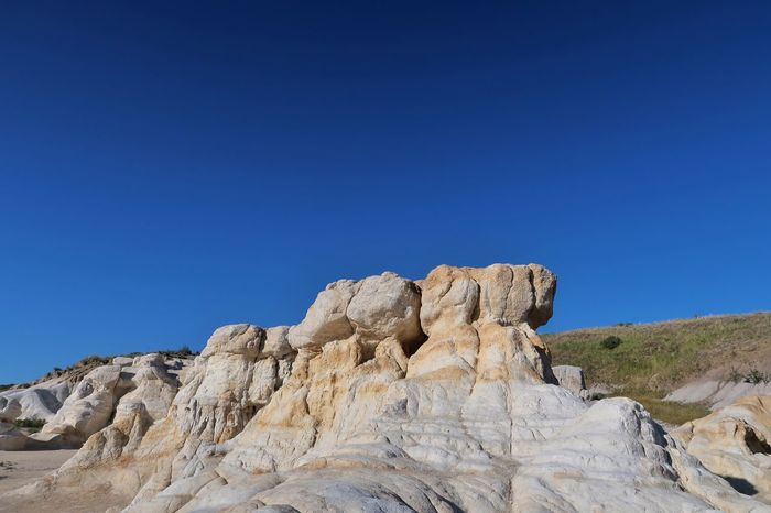 Landscape of white and yellow rock formations in Colorado - paint Mines Interpretive Park Paint Mines Interpretive Park Colorado Unusual View Colorful Rocks Sky Blue Clear Sky Tranquility Nature Beauty In Nature Scenics - Nature Day Rock Copy Space Low Angle View Solid Land Rock - Object No People Sunlight Non-urban Scene Rock Formation Tranquil Scene Environment