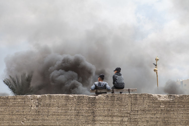 Two palestinians are watching burning tyres in Ramallah during clashes for Nakba day commemoration, on the 15th of May in Palestine. Middle East The Photojournalist - 2018 EyeEm Awards Adult Architecture Building Exterior Built Structure Communication Day Documentary Journalism Leisure Activity Lifestyles Men Nature Outdoors People Real People Reportage Sign Sitting Sky Smoke - Physical Structure Togetherness Two People Young Men