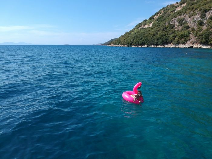 Woman swimming with pink inflatable ring in sea during sunny day