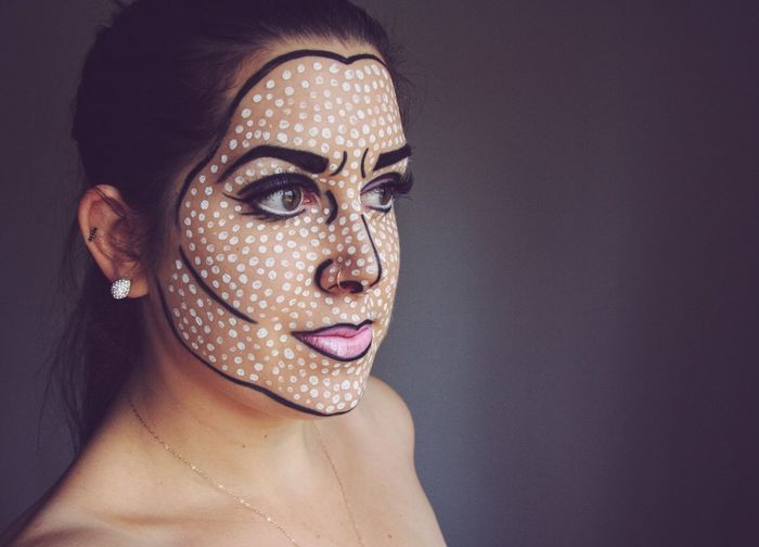 Close-Up Of Young Woman With Face Paint While Standing On Gray Background