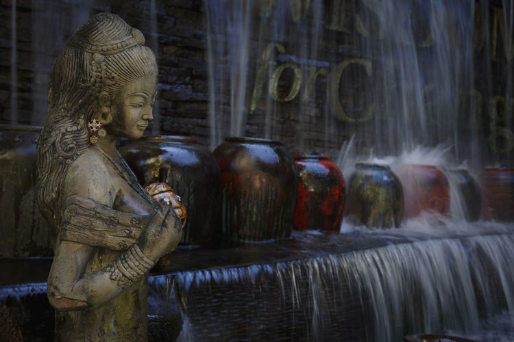 Statue against blurred flowing water