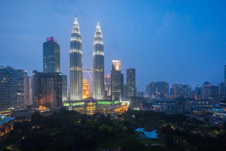 Illuminated petronas towers in city against clear blue sky at dusk