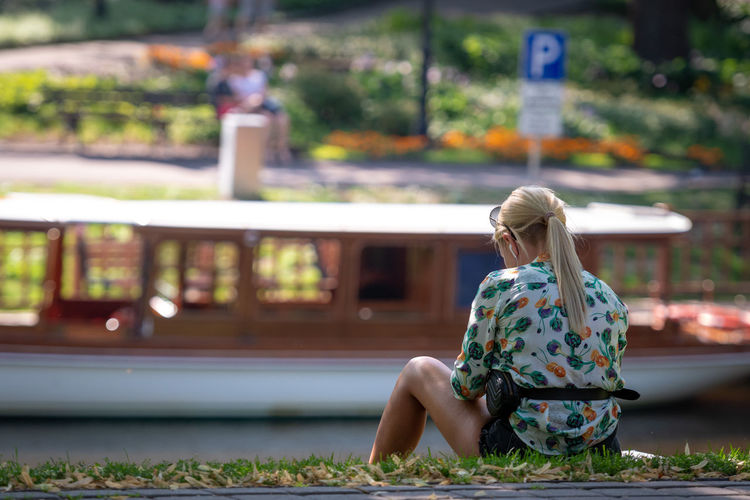 Rear view of woman sitting on grass by lake