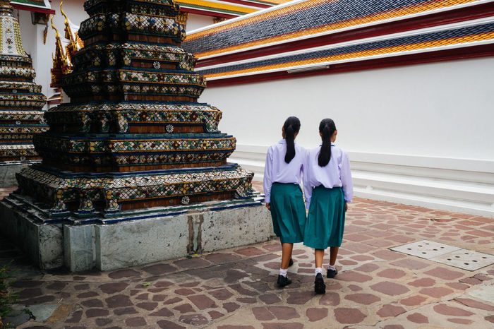 FULL LENGTH REAR VIEW OF PEOPLE WALKING OUTSIDE TEMPLE