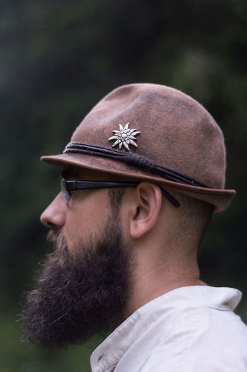 Close-Up Side View Of Young Man Wearing Eyeglasses And Hat