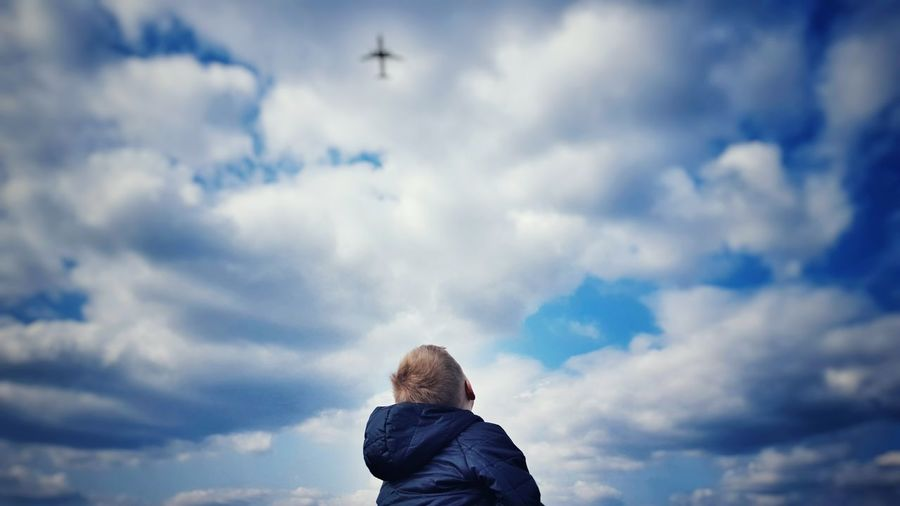 Low Angle View Of Boy Standing Against Cloudy Sky