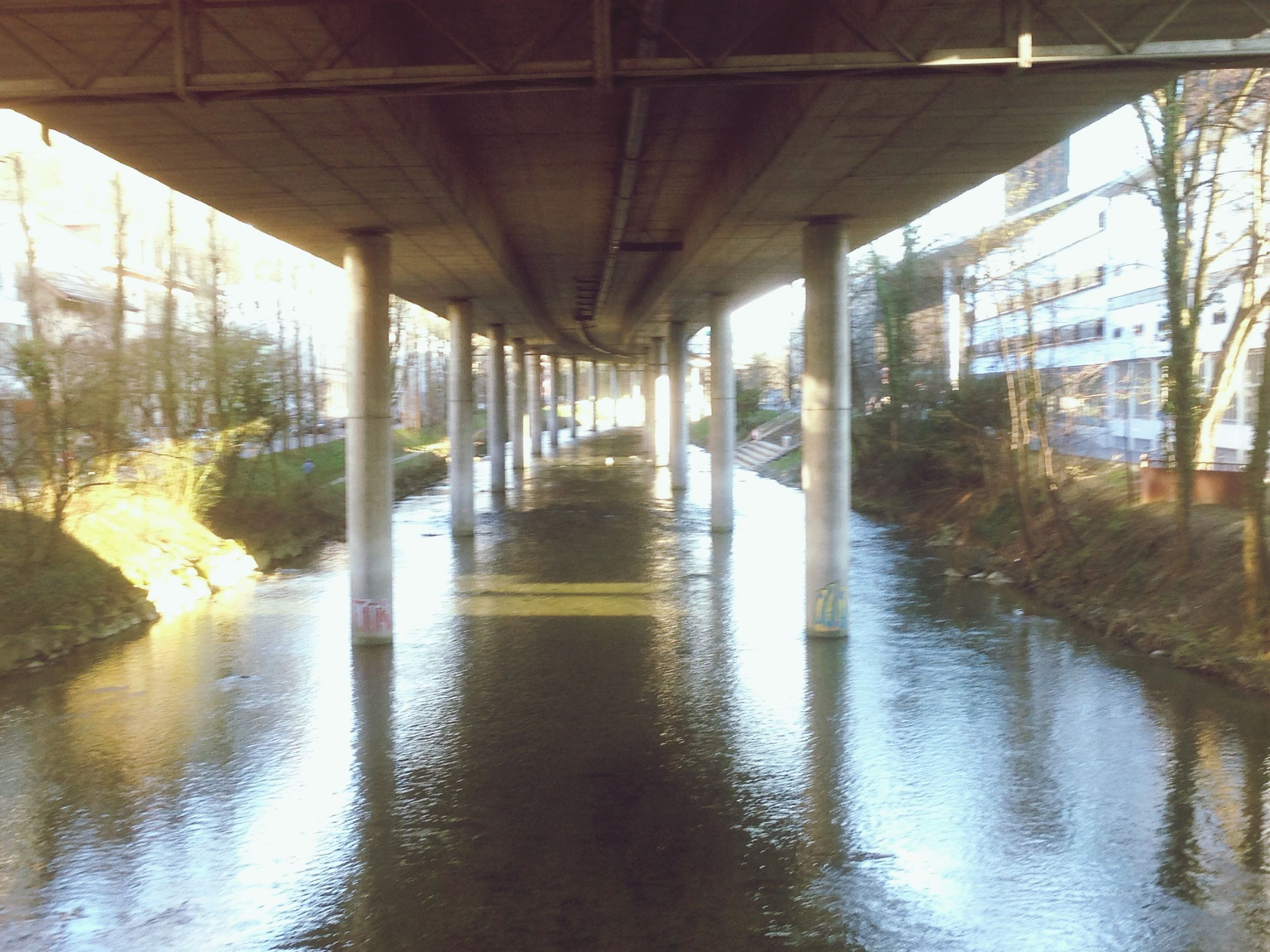 built structure, architecture, water, reflection, indoors, architectural column, bridge - man made structure, connection, sunlight, window, no people, day, waterfront, column, support, glass - material, below, nature, diminishing perspective, river