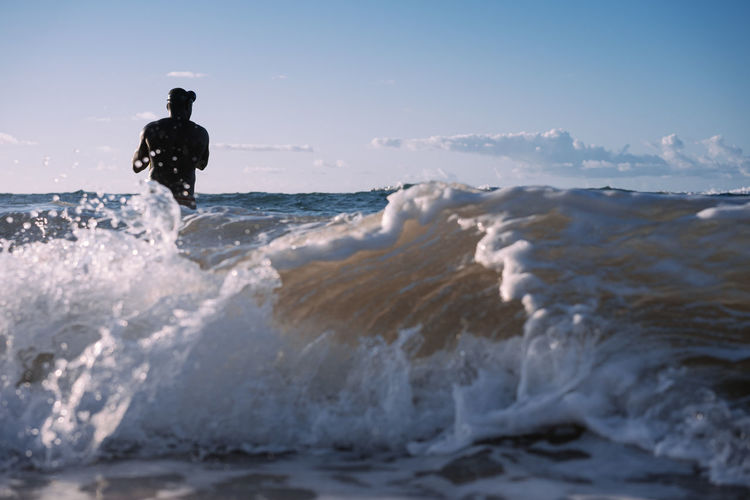 Man surfing on beach against sky