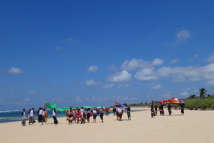 People with flag at beach against blue sky