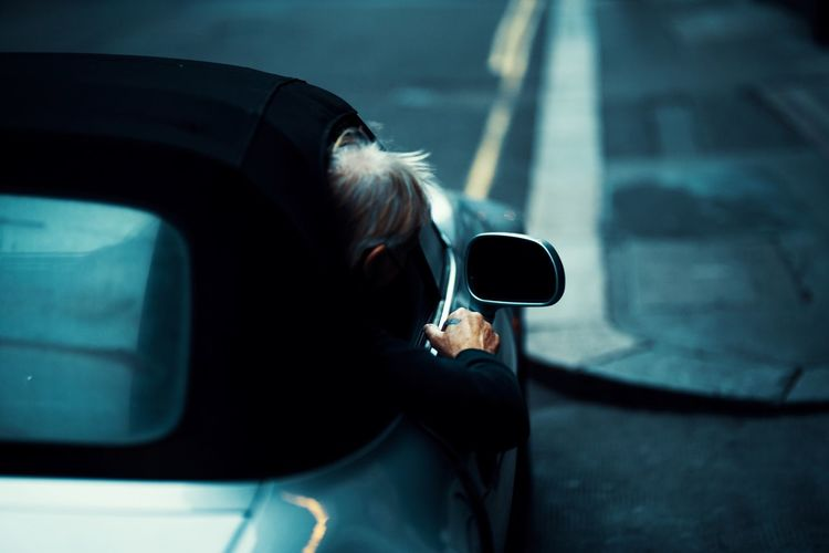 Rear view of man leaning out of car window