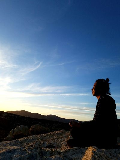Side View Of Silhouette Man Meditating On Cliff Against Sky At Sunset
