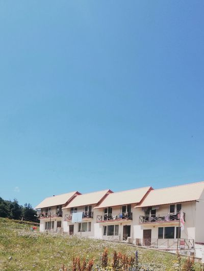 Houses by buildings against clear blue sky