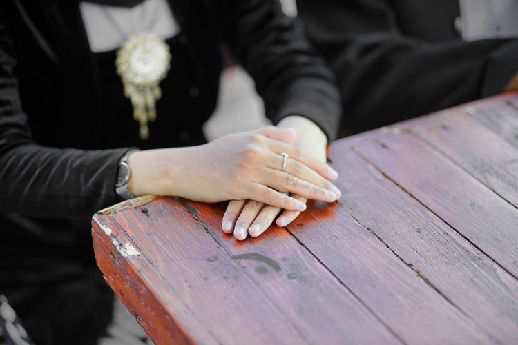 Close-up of couple hands on table