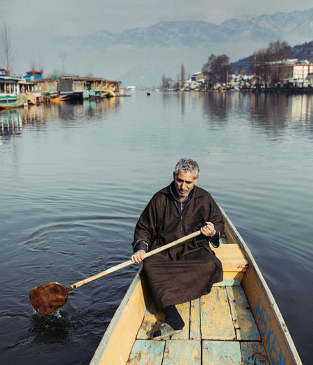 Portrait of man with fishing rod standing on lake