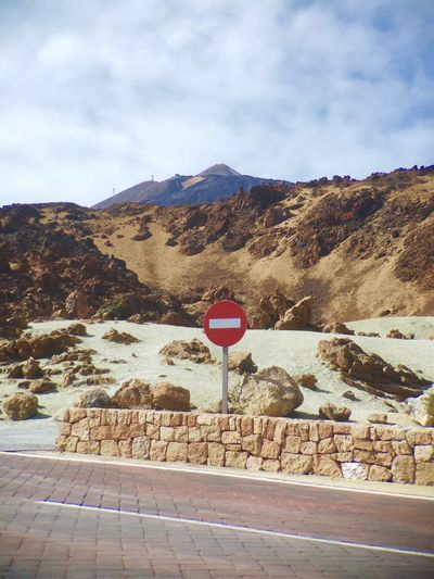 Stop Sign By Mountain Against Sky