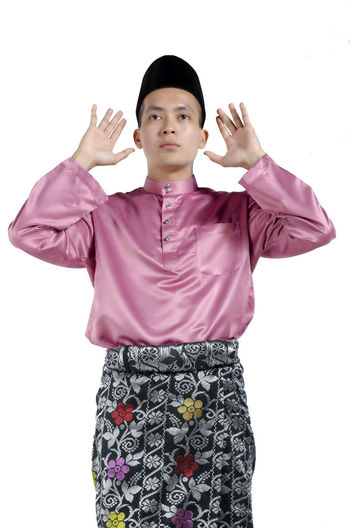 Portrait of young and handsome asian man with traditional clothing during hari raya over white background Studio Shot White Background Front View Indoors  Standing Three Quarter Length One Person Cut Out Looking At Camera Casual Clothing Portrait Gesturing Young Adult Waist Up Women Clothing Young Women Human Arm