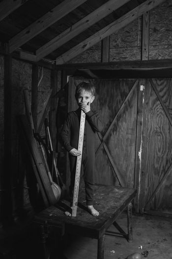 Portrait Of Boy With Yardstick On Table In Wooden Garage