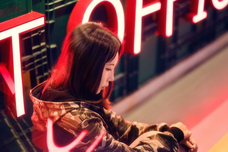 Side view of thoughtful woman sitting by neon sign at night