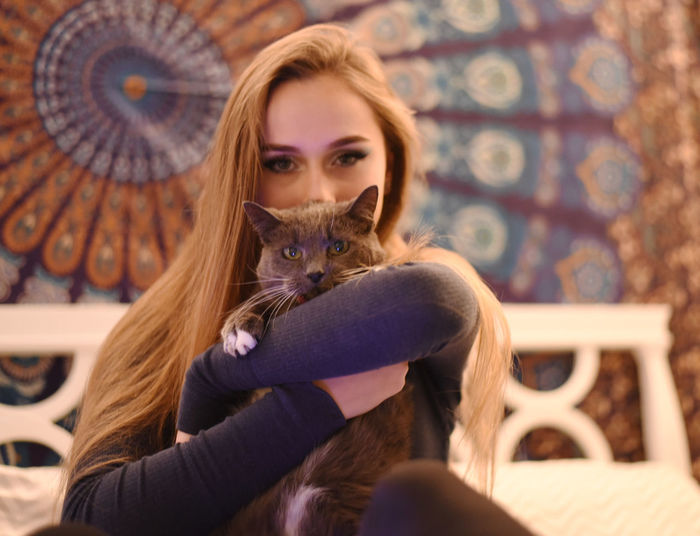 Portrait of beautiful young woman sitting with cat at home