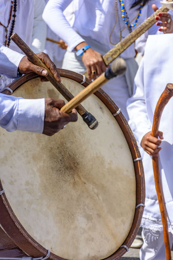 Midsection of man playing drum by crowd during festival