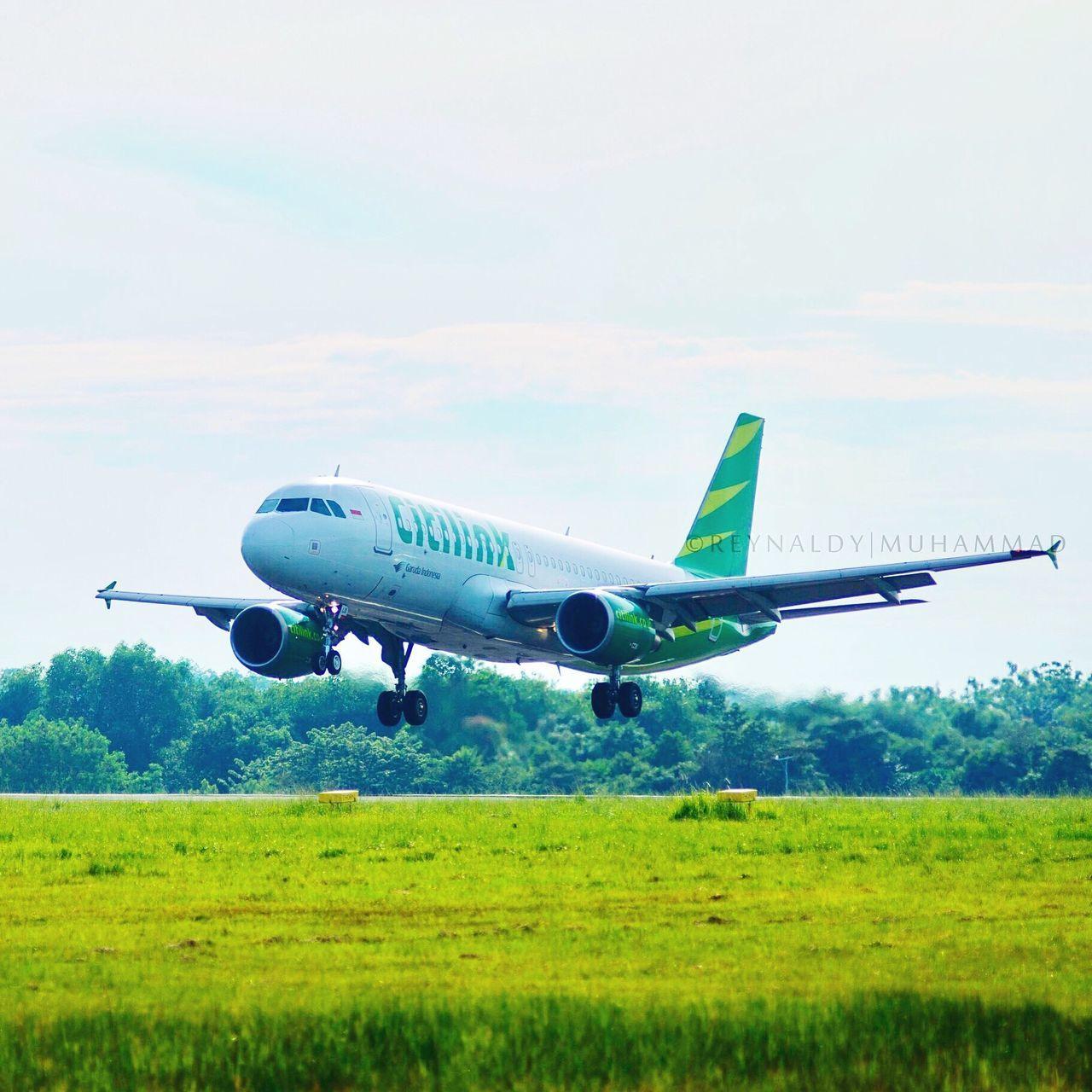 AIRPLANE FLYING OVER RUNWAY