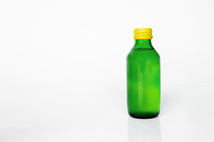 Close-up of green bottle against white background