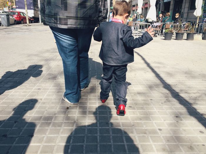 Low section of father with son walking on footpath