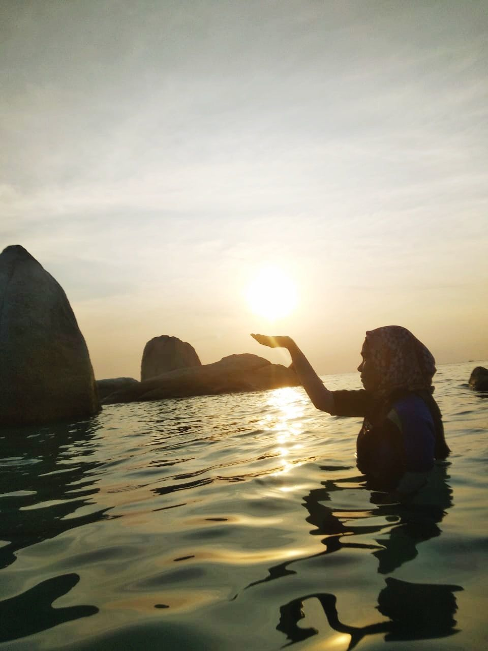 water, sky, beauty in nature, sunset, real people, rock, sea, nature, waterfront, rock - object, sun, tranquility, solid, one person, tranquil scene, scenics - nature, women, adult, leisure activity, outdoors
