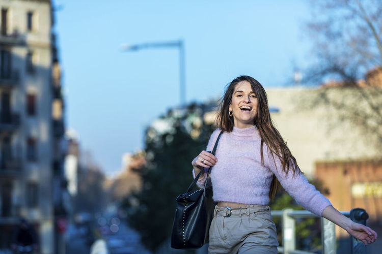 Portrait of smiling woman walking in city