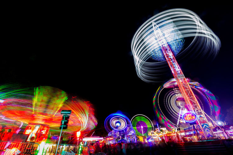 Fairground ride light trails at Witney Feast including 'Air', 'SkyFlyer', 'Extreme', 'Storm' and 'Megaspin' 'Air' 'Extreme' 'SkyFlyer' Fairground Attraction Funfair Nightphotography Amusement Park Amusement Park Ride Blurred Motion Enjoyment Excitement Fairground Fairground Ride Ferris Wheel Funfair Ride Illuminated Leisure Activity Light Trail Long Exposure Motion Multi Colored Night Ride Speed Spinning