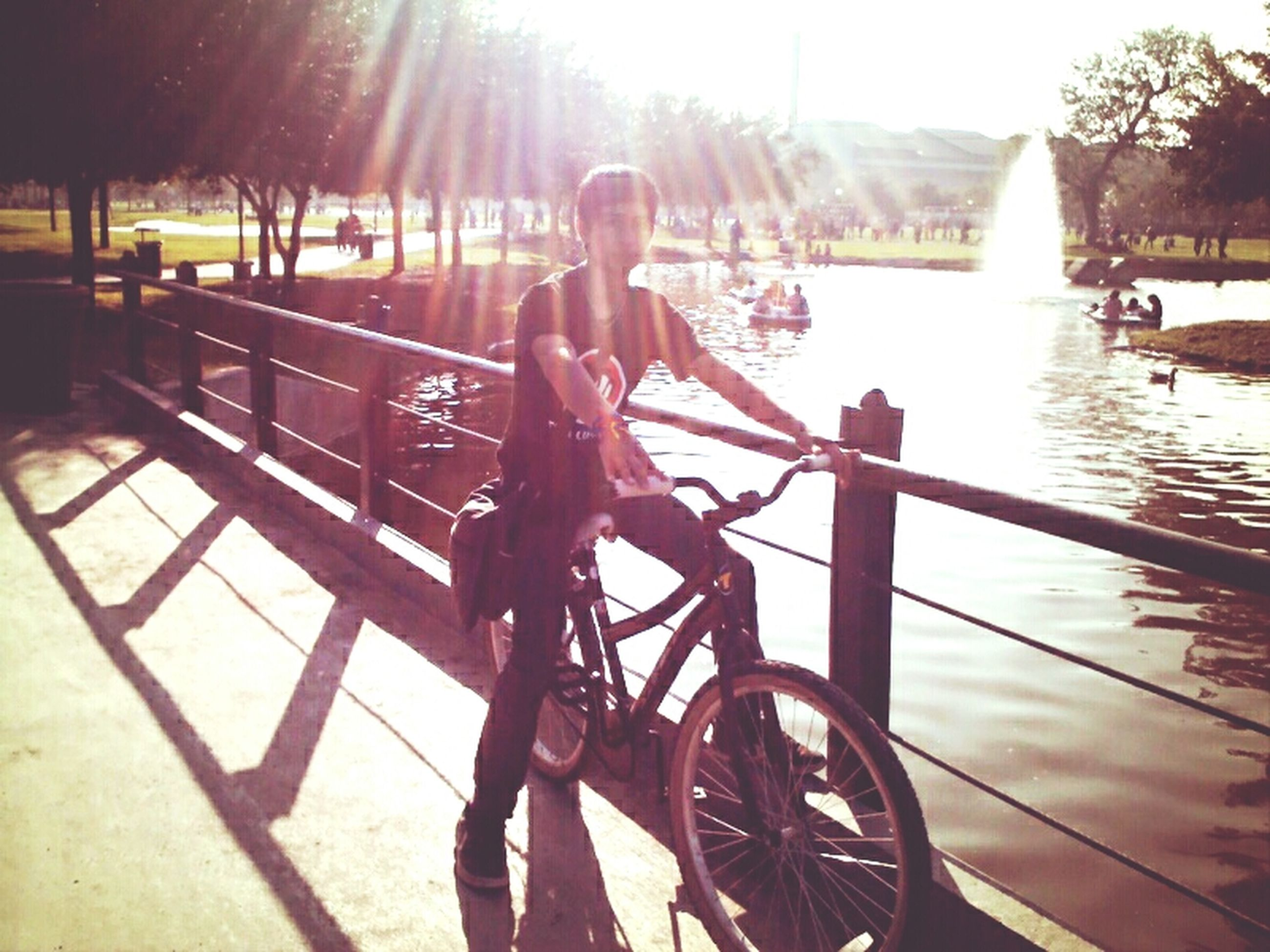 sunlight, sunbeam, sun, leisure activity, lens flare, bicycle, lifestyles, sunny, shadow, railing, water, transportation, outdoors, men, mode of transport, day, nature, wood - material