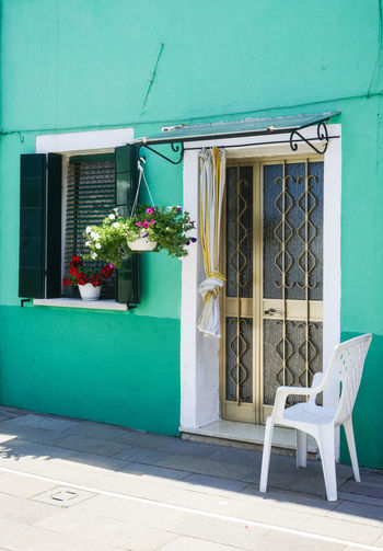 COME HAVE A SEAT Basic BeautyCityCitylifeItaliaItalySimplicityUrbanVacationAbsence Architecture Brick Wall Building Exterior Built Structure Chair Closed Door Entrance Potted Plant Wall Pastel Colors Pastel Walls