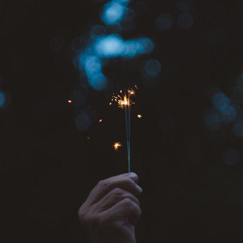 Cropped hand holding illuminated sparkler at night