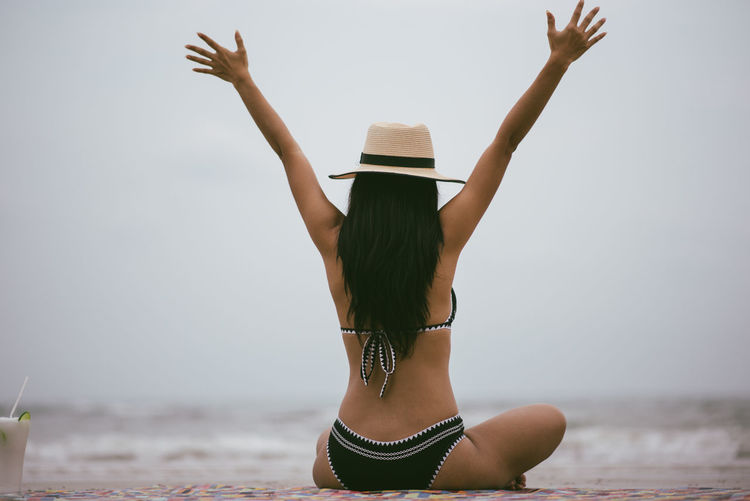 Water Sea Leisure Activity One Person Clothing Young Women Real People Rear View Young Adult Lifestyles Hat Beach Sky Holiday Three Quarter Length Bikini Arms Raised Land Vacations Horizon Over Water Hairstyle Human Arm Hair Fashion Sun Hat