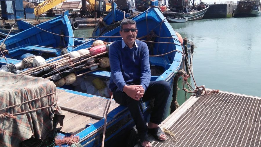 Portrait of man sitting on boat moored at harbor